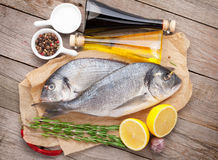 Fresh dorado fish cooking with spices and condiments. On wooden table Royalty Free Stock Image