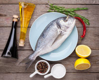 Fresh dorado fish cooking with spices and condiments. On wooden table Stock Photography