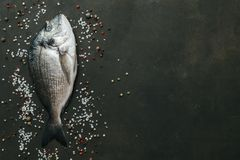 Fresh dorado fish. Delicious fresh fish with spices on dark vintage background. Top view Stock Photo