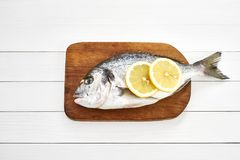 Fresh dorado fish with lemon on wooden cutting board on white wooden table. Top view. Copy space Royalty Free Stock Photography