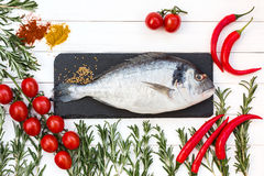 Fresh dorado fish, rosemary, cherry tomatoes, chilly pepper on white wooden table. Top view. Stock Photography