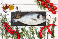 Fresh dorado fish, rosemary, cherry tomatoes, chilly pepper on white wooden table. Top view. Stock Image
