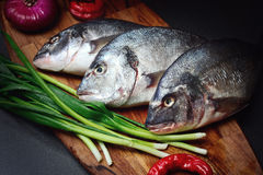 Fresh Dorado fish on a wooden board with vegetables. Stock Photo