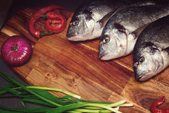 Fresh dorado fish on a wooden board with vegetables in a dark key Royalty Free Stock Image