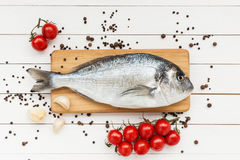 Fresh dorado fish on wooden cutting board with cherry tomatoes Royalty Free Stock Photography