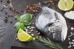Fresh dorado fish on wooden cutting board. And ingredients. Dorado, lime, herbs and spices Stock Photos