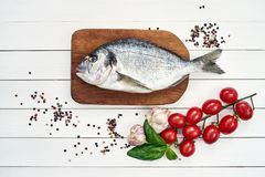 Fresh dorado fish on wooden cutting board with garlic, tomatoes, basil and peppercorns. Top view, copy space Stock Photos