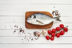 Fresh dorado fish on wooden cutting board with garlic, tomatoes and peppercorns. Top view, copy space Royalty Free Stock Photo