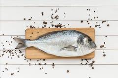 Fresh dorado fish on wooden cutting board with peppercorns. Dorado fish on wooden cutting board with peppercorns Stock Photo