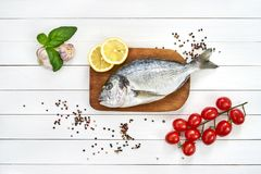 Fresh dorado fish on wooden cutting board with tomatoes, lemon, basil and garlic on white wooden table. Top view. Fresh dorado fish on wooden cutting board with Royalty Free Stock Photos