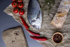 Fresh dorado fish on wooden cutting board with tomatoes and pepper. Dorado fish on slate board with cherry tomatoes, lemon, garlic, rosemary, chilly pepper and Stock Images