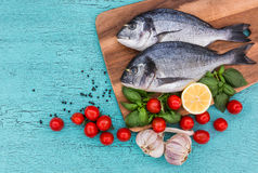 Fresh dorado fish on wooden cutting board and vegetables on blue table. Top view Stock Images