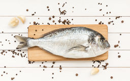 Fresh dorado fish on wooden kitchen board, white wooden table. Fresh dorado fish on wooden cutting board with garlic. Top view Stock Image