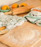 Fresh dough on the board with flour, chequered and striped towel Stock Photo