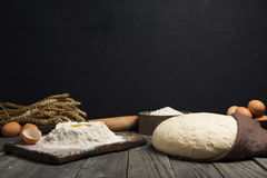 Fresh dough with flour and eggs on wooden table Stock Image