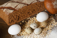 Fresh dough in flour with rye bread. Fresh dough with flour on a paper napkin decorated with rye bread flour, quail eggs and wheat grains Stock Image