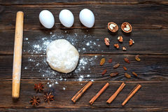 Fresh dough ready for baking on rustic wooden background. Fresh dough ready for baking with rolling pin, flour, eggs, nuts, cinnamon, raisins, fennel on rustic Stock Photo