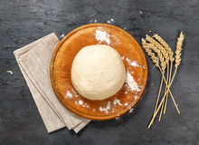 Fresh dough on wooden round board with ears of wheat Royalty Free Stock Photography