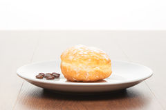 Fresh doughnut with icing sugar and coffee beans on white ceramic plate on bright light brown wooden table royalty free stock photo