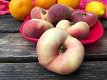 Fresh doughnut peaches fruits in closeup. On a pink plate Stock Images