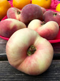 Fresh doughnut peaches fruits in closeup. On a pink plate Royalty Free Stock Image