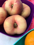 Fresh doughnut peaches fruits in closeup. In a purple bowl Royalty Free Stock Images