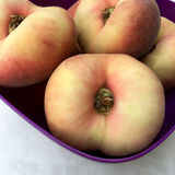 Fresh doughnut peaches fruits. In closeup in a purple bowl Royalty Free Stock Images