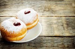 Fresh doughnuts with jam for Hanukkah. Fresh doughnuts with jam on a dark wood background for Hanukkah. tinting. selective focus on the front donut