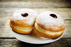Fresh doughnuts with jam for Hanukkah. Fresh doughnuts with jam on a dark wood background for Hanukkah. tinting. selective focus on the right donut royalty free stock photography