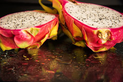 Fresh dragon fruit cut in half on a on black background. Royalty Free Stock Photos
