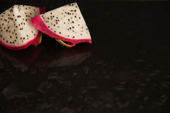 Fresh dragon fruit in cut into pieces on a on black background Stock Photo