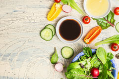 Fresh dressing and organic lettuce and vegetables for healthy salad on light rustic kitchen table, top view, place for text. Stock Photos