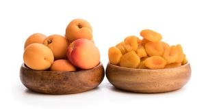Fresh and dried apricot in wooden bowls stock image