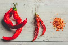 Fresh, dried and crushed red chili pepper. Over colored wooden background royalty free stock photography
