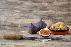 Fresh and dried figs on wood. Sweet fresh whole and cut figs and dried figs in a bowl Royalty Free Stock Photos