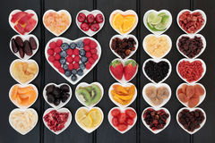 Fresh and Dried Fruit. Fresh and dried mixed fruit superfood selection in heart shaped bowls over wooden black background Stock Image