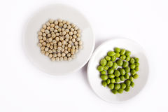 Fresh and dried green peas on plate Royalty Free Stock Images