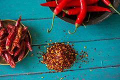 Fresh and dried hot chilli in bowl and seeds on table Stock Photos