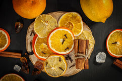 Fresh and dried oranges and lemons on a black surface Stock Image