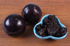 Fresh and dried plums in blue bowl on wooden table, healthy food Royalty Free Stock Photos