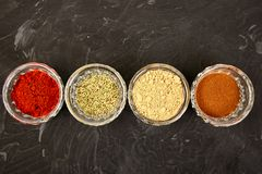 Fresh and dried seasoning herbs and spices. Paprika, ginger, cinnamon, rosemary in bowls. Colourful various herbs and spices for cooking on black background royalty free stock photo