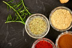 Fresh and dried seasoning herbs and spices. Paprika, ginger, cinnamon, rosemary in bowls. Colourful various herbs and spices for cooking on black background stock image