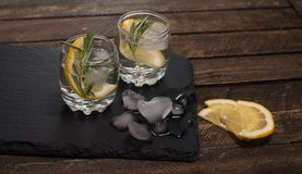 Fresh drink with lemon and rosemary on slate board on wooden bac Royalty Free Stock Image