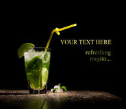 Fresh drink with lime. Mint and ice on wooden table on black background royalty free stock photos