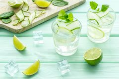 Fresh drink with lime, mint, spinach, cucumber and ice on mint green background. Fresh healthy fruit drink with lime, mint, spinach, cucumber and ice on mint royalty free stock photography