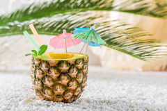 Fresh drink in pineapple with cocktail umbrellas Stock Image
