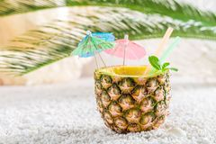 Fresh drink in pineapple with cocktail umbrellas. On white pebbles stock photography