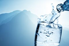Fresh drinking water is poured in a glass against the background of mountains royalty free stock image