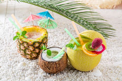 Fresh drinks in fresh fruits on sandy beach Royalty Free Stock Images