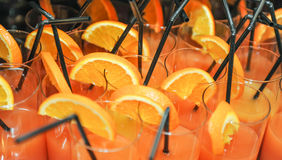 Fresh drinks with orange slices and straws, close up. Orange juice in glasses with straws, ready to be drunk Stock Photos